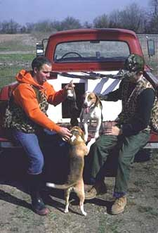 Two hunters play with their hunting dogs
