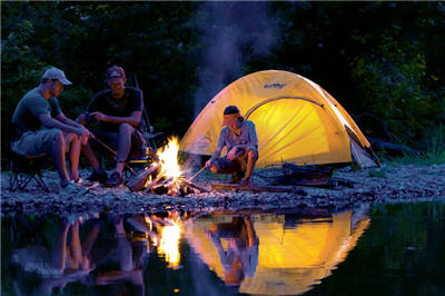 Campers on a river bank at night sitting next to a campfire