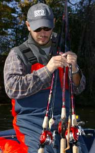 Angler holding an assortment of fishing rod & reel combos