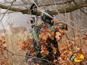 Bow hunting in a treestand drawing his bow