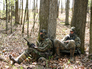 2 Turkey hunting partners leaning on separate trees calling turkeys