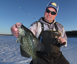Jason Mitchell holding a large crappie on a frozen lake