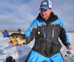 Jason Mitchell holding Bluegill caught while ice fishing.