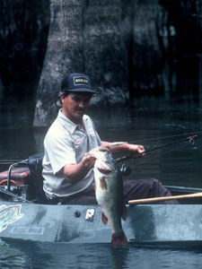Bass angler holding up a large pond bass