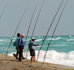 Three surf anglers on the beach fishing