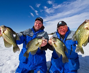 Two ice anglers holding up the crappie the caught