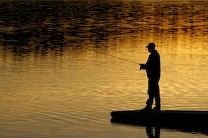Fishing on a dock at sunset