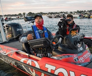 Fishing pro Mike Iaconelli with trophy sitting in his tournament bass boat with a cameraman