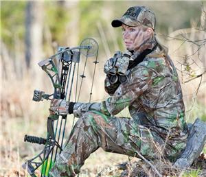 Female bowhunter sitting next to tree with her compound bow