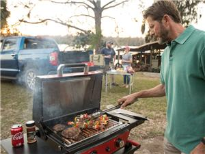 Man staning at an outdoor grill at a campsite grilling meat and vegitables