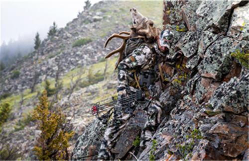 Deer hunter climbing up rocks with a buck's head strapped to his back