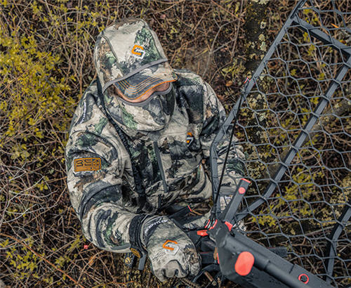 Deer hunter on the ground setting up a treestand wearing a Scent-Lok BE:1 Voyage Jacket