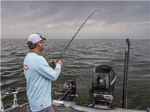 Keith Kavajez standing in the back of a boat jig trolling for walleye