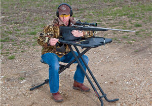 Hunter sitting at a gun shooting stand target shooting for practice