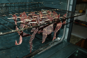 Jerky meat hanging from a tray