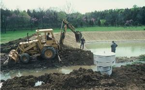 Men digging a farm pond hole