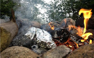 Foil pack food cooking in a campfire