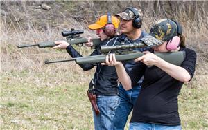 Young shooters practice shooting rifles