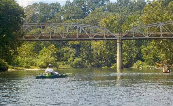Two people in kayaks floating a river in Missouri towards a bridge crossing