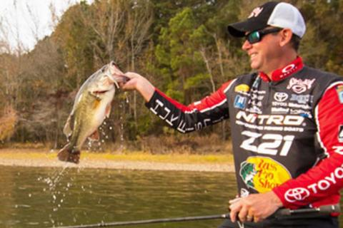 Kevin VanDam during fishing tournament holding up a bass