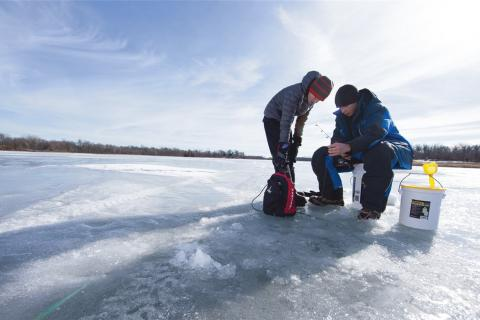 Two ice anglers ice fishing on a frozen lake