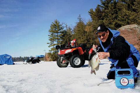 Ice angler on a frozen lake fishing crappie