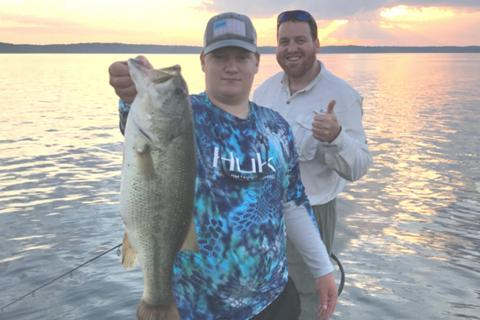 Two bass anglers on Kentucky lake, one with a bass
