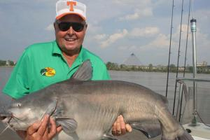 Bill Dance standing on a boat with a large blue catfish