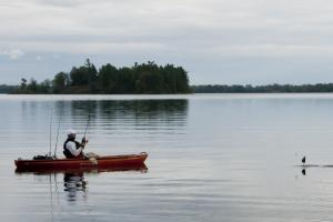 Angler on a lake reeling in a fish from his kayak