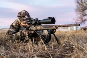Coyote hunter in camo with a high power scope