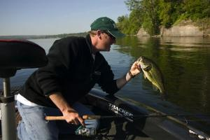 Angler with spinning rod and reel leaning over boat lifing up a largemouth bass