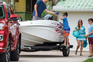 Family of four loading a boat with boating gear for a trip to the lake