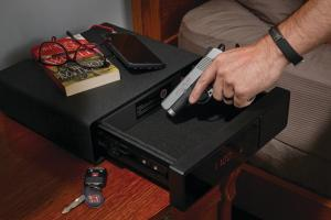Placing gun into a bedside handgun vault