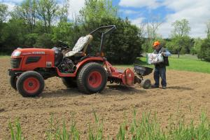 Land owner is loading seed spreader behind his tractor  to plant a food plot