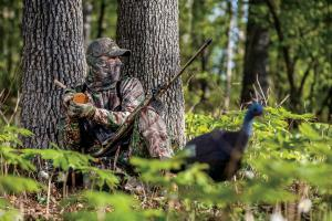 Turkey hunter leaning up to a tree using a turkey friction call