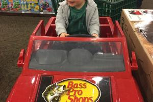 Toddler boy sitting in an electic bass pro chevy truck in toy section of a Bass Pro retal store.