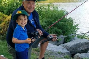 Young angler fishing with grandfather