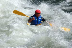 Kayaker in the middle of whitewater paddleing the rapids