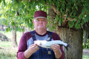 Angler hold a White Catfish under a shade tree