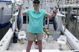Lady angler holding up two of may blackfin tuna she caught