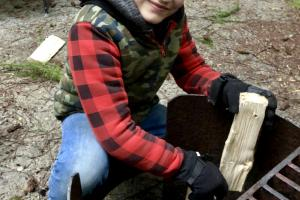 Young camper is building a camp fire