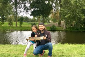 Father - daughter holding up a young norther pike on a summer day near the waters edge