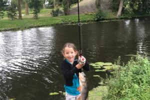 Small girl wih rod and reel at  edge of pond hold up her fish