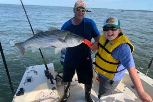 Family fishng striped bass is proud of this nice catch