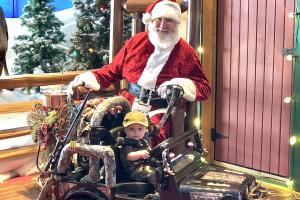 Toddler in toy jeep getting hisphoto with Santa at Bass Pro