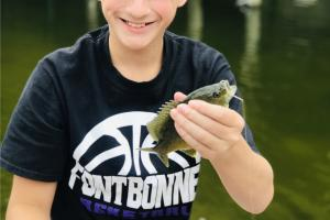Boy angler hold up a small perch at Bass Pros gone fishing event