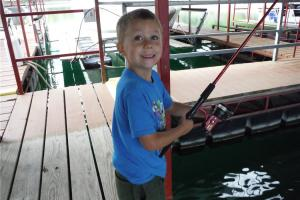 Young boy fishing from a boat dock
