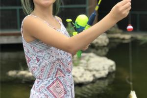 Young girl hold up a fish she caught at Bass Pros gone fishing event