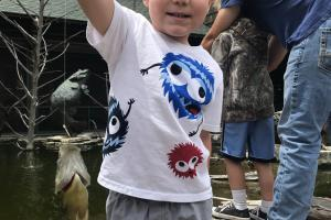 Young Jax holding up a fish at Bass Pro's kids fishing day