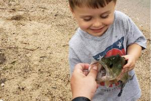 Small angler holding a bass looking into its mouth